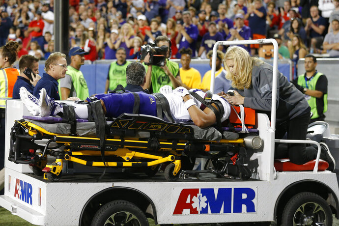 Washington linebacker MJ Tafisi (53) gets taken off the field after an injury in the second half during an NCAA college football game against Arizona, Saturday, Oct. 12, 2019, in Tucson, Ariz. (AP Photo/Rick Scuteri)