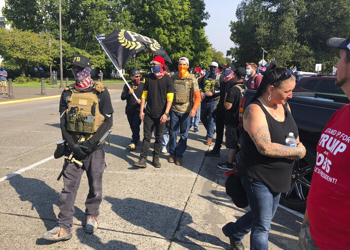 "FILE - Members of the extremist right-wing group the Proud Boys arrive in Salem, Ore., on Monday Sept. 7, 2020 for a pro-Donald Trump rally at the Capitol. President Trump on Tuesday, Sept. 29, 2020 didn't condemn white supremacist groups and their role in violence in some American cities this summer, branding it solely a ""left-wing"" problem and telling one far-right extremist group to ""stand back and stand by."" (AP Photo/Andrew Selsky)"