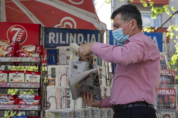 Vendor Ibrahim Gashi, arranges weekly and monthly magazines at his newspaper kiosk were he has been selling newspapers downtown for 35 consecutive years except one, in the capital Pristina, Thursday, April 29, 2021. The printing presses stopped running at the start of the pandemic in Kosovo. The country's five dailies all stopped printing physical newspapers and turned into online media portals. But these do not reach all the people as before, and many fear they prioritise speed over accuracy.  (AP Photo/Visar Kryeziu)