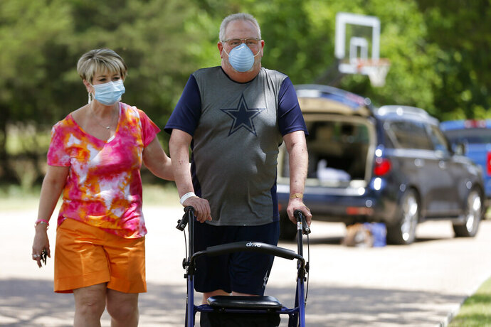 Terri Donelson, left, and her husband, Stephen, walk up their driveway to see friends and family awaiting him at his home in Midlothian, Texas on Friday, June 19, 2020, after his 90-day stay in the Zale Hospital on the UT Southwestern Campus. Donelson's family hadn't left the house in two weeks after COVID-19 started spreading in Texas,hoping to shield the organ transplant recipient. Yetone night, his wife found him barely breathing, his skin turning blue,and called 911. (AP Photo/Tony Gutierrez)