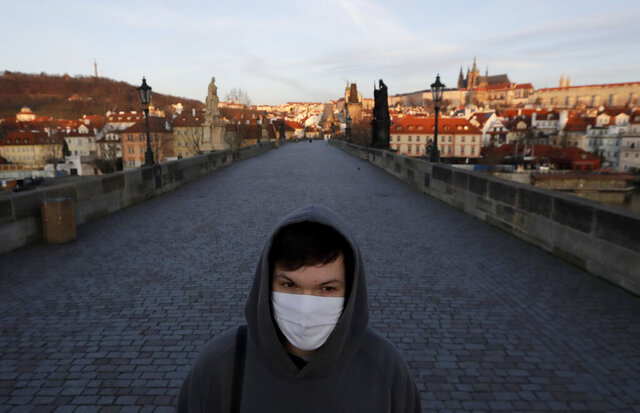 FILE - In this March 16, 2020 file photo a young man wearing a face mask walks across an empty Charles Bridge in Prague, Czech Republic. Czechs had been assured it wouldn't happen again. But amid a record surge of coronavirus infections that's threatening the entire health system with collapse, the Czech Republic is adopting on Thursday exactly the same massive restrictions it slapped on citizens in the spring. Prime Minister Andrej Babis had repeatedly said these measures would never be repeated.(AP Photo/Petr David Josek, File)