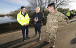 Britain's Prime Minister Boris Johnson, centre, talks with Lt Col Tom Robinson, right, from the Light Dragoons and an Environment Agency official during a visit to see the effects of recent flooding, in Stainforth, England, Wednesday, Nov. 13, 2019. (Danny Lawson/Pool Photo via AP)