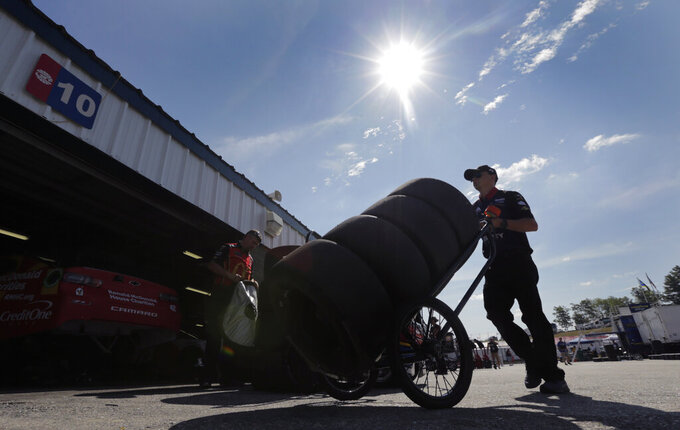 A crew worker for driver William Byron wheels a cart loaded with tires to their garage prior to a NASCAR Cup Series auto race practice at New Hampshire Motor Speedway in Loudon, N.H., Saturday, July 20, 2019. (AP Photo/Charles Krupa)