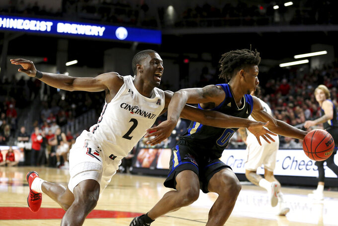 Cincinnati guard Keith Williams (2) reaches for a steal on Tulsa guard Brandon Rachal (0) during the first half of an NCAA college basketball game Wednesday, Jan. 8, 2020, in Cincinnati. (Kareem Elagazzar/The Cincinnati Enquirer via AP)