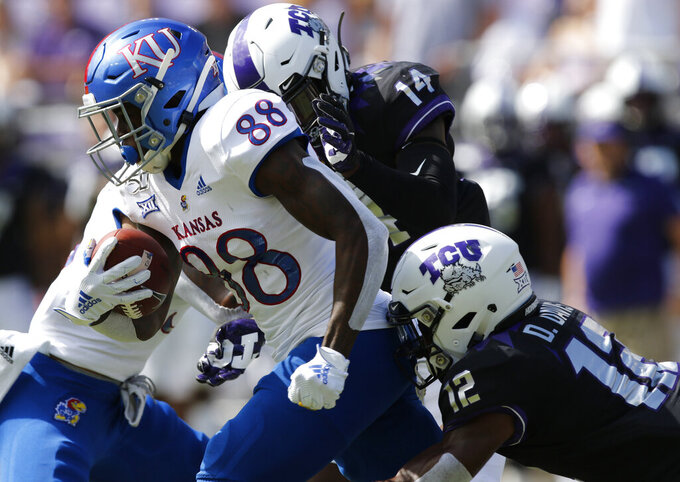 Kansas wide receiver Jamahl Horne (88) carries the ball after a catch, pursued by TCU  linebacker DeMauryon Holmes (14) and cornerback Jeff Gladney (12) during an NCAA college football game in Fort Worth, Texas Saturday, Sept. 28, 2019.  (David Kent/Star-Telegram via AP)
