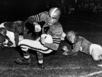 File-This Sept.10, 1954, file photo shows quarterback Otto Graham,14, of the Cleveland Browns, spinning around and evades his tackler and scores Browns' first touchdown in the first quarter of exhibition against the Detroit Lions. Members of a special panel of 26 selected all of them for the position as part of the NFL's celebration of its 100th season. All won league titles except Marino. All are in the Hall of Fame except Brady and Manning, who are not yet eligible.  On Friday, Dec. 27, 2019, quarterback was the final position revealed for the All-Time Team. (AP Photo/Dallas Morning News, File)