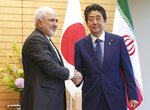 Iranian Foreign Minister Mohammad Javad Zarif, left, and Japanese Prime Minister Shinzo Abe, right, shake hands at Abe's official residence in Tokyo Thursday, May 16, 2019. (AP Photo/Eugene Hoshiko, Pool)