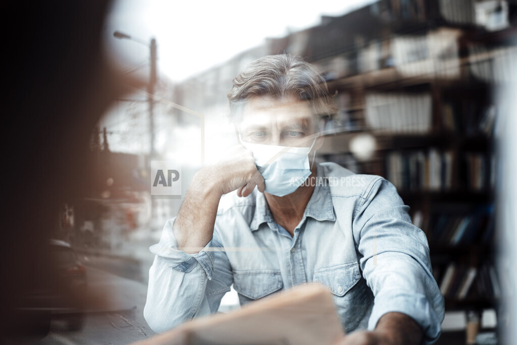 Mature man wearing protective face mask reading newspaper in cafe seen through glass window