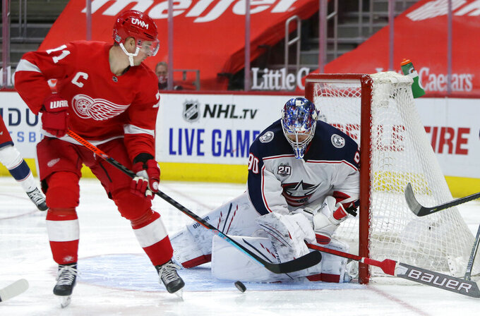 CORRECTS DETROIT PLAYER TO DYLAN LARKIN, INSTEAD OF FILIP ZADINA - Columbus Blue Jackets goaltender Elvis Merzlikins (90) stops a shot by Detroit Red Wings center Dylan Larkin (71) during the second period of an NHL hockey game Tuesday, Jan. 19, 2021, in Detroit. (AP Photo/Duane Burleson)
