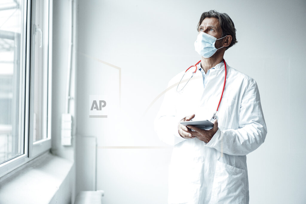 Male doctor wearing protective face mask holding digital tablet while standing by window in clinic