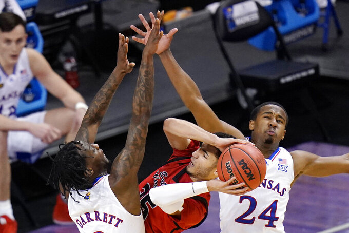 Eastern Washington guard Michael Meadows, center, gets pressure from Kansas guard Marcus Garrett (0) and teammate Bryce Thompson (24) while attempting to shoot during the first half of a first-round game in the NCAA college basketball tournament at Farmers Coliseum in Indianapolis, Saturday, March 20, 2021. (AP Photo/AJ Mast)