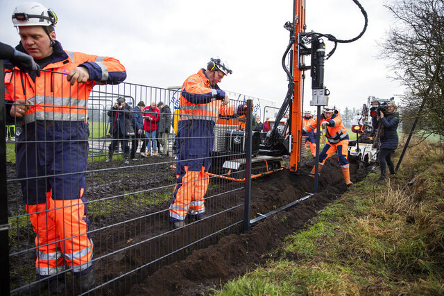 FILE - In this Monday Jan. 28, 2019 file photo, workers erect a fence along the Denmark Germany border at Padborg, Denmark. Officials say the number of wild boars in Denmark has fallen since a 70-kilometer (43.4-mile) fence was erected along the German border to protect the valuable Danish pork industry. The fence was put up last year in an attempt to prevent wild swine crossing from Germany and breeding with farm pigs or possibly passing disease. (Frank Cilius/Ritzau Scanpix via AP, File)