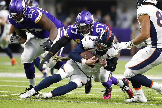 Denver Broncos quarterback Brandon Allen, center, is sacked by Minnesota Vikings defensive end Everson Griffen (97) during the second half of an NFL football game, Sunday, Nov. 17, 2019, in Minneapolis. (AP Photo/Bruce Kluckhohn)