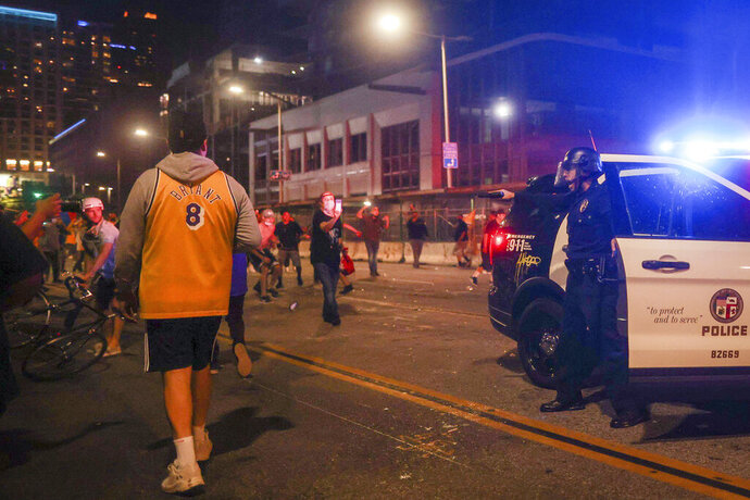 Los Angeles Lakers fans celebrate outside of Staples Center as Los Angeles Police Department officers try to disperse them, Sunday, Oct. 11, 2020, in Los Angeles, after the Lakers defeated the Miami Heat in Game 6 of basketball's NBA Finals to win the championship. (AP Photo/Christian Monterrosa)