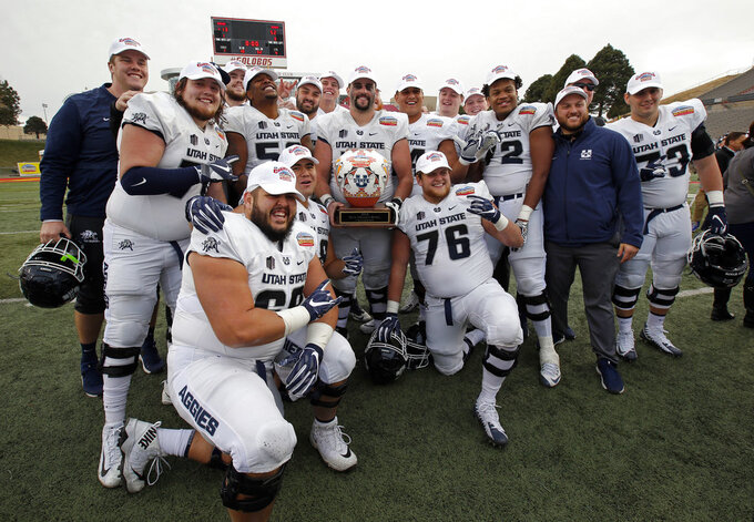Utah State players pose with the trophy after their victory over North Texas in the New Mexico Bowl NCAA college football game in Albuquerque, N.M., Saturday, Dec. 15, 2018. (AP Photo/Andres Leighton)