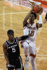 Texas' Donovan Williams (10) drives against Kansas State's Rudi Williams (5) during the first half of an NCAA college basketball game in Austin, Texas, Saturday, Jan. 16, 2021. (AP Photo/Chuck Burton)