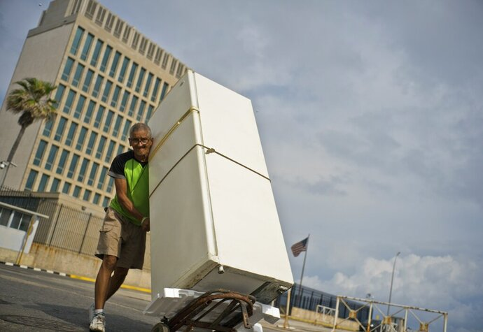 A man pushes a refrigerator on a dollie past the U.S. embassy, behind, in Havana, Cuba, Monday, March 18, 2019. The U.S. State Department said Friday, March, 15, 2019, that it is eliminating a coveted five-year tourist visa for Cubans, dealing a heavy blow to entrepreneurs and Cuban members of divided families, who used the visas to see relatives in the U.S. and buy precious supplies for their businesses on the island. (AP Photo/Ramon Espinosa)