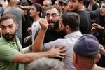 Anti-government protesters and Hezbollah supporters clash during a protest in Beirut, Lebanon, Friday, Oct. 25, 2019. Leader of Lebanon's Hezbollah calls on his supporters to leave the protests to avoid friction and seek dialogue instead. (AP Photo/Hassan Ammar)