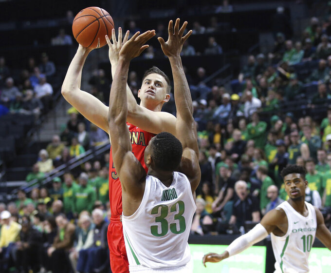 Arizona's Jake DesJardins shoots over Oregon's Francis Okoro, with Victor Bailey Jr., right, watching during the second half of an NCAA college basketball game Saturday, March 2, 2019, in Eugene, Ore. (AP Photo/Chris Pietsch)