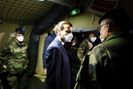 French President Emmanuel Macron, center, wears a face mask as he visits the military field hospital in Mulhouse, eastern France, Wednesday, March 25, 2020. French President Emmanuel Macron launched a special military operation Wednesday to help fight the new virus in one of the world's hardest-hit countries. The new coronavirus causes mild or moderate symptoms for most people, but for some, especially older adults and people with existing health problems, it can cause more severe illness or death. (Mathieu Cugnot/Pool via AP)