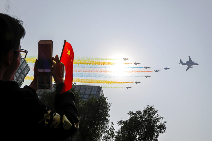 A man uses his smartphone to film Chinese military planes trail colored smoke as they fly in formation past the sun during a parade to commemorate the 70th anniversary of the founding of Communist China in Beijing, Tuesday, Oct. 1, 2019. China's Communist Party is celebrating its 70th anniversary in power with a parade showcasing its economic development and newest weapons. The event marks the anniversary of the Oct. 1, 1949, announcement of the founding of the People's Republic of China by then-leader Mao Zedong. (AP Photo/Andy Wong)