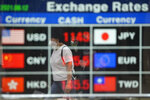A woman wearing a face mask is reflected on an electronic foreign currency exchange rates in downtown Seoul, South Korea, Thursday, Aug. 12, 2021. Asian shares were mixed Thursday as caution set in among investors following another wobbly day of trading on Wall Street.(AP Photo/Lee Jin-man)