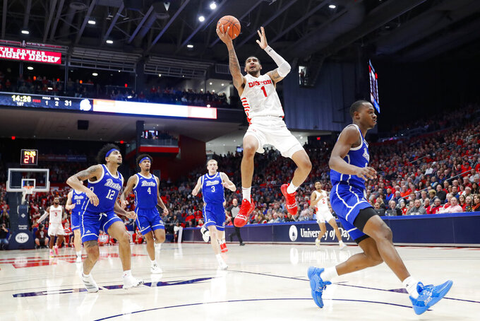 Dayton's Obi Toppin (1) shoots on a break-away as Drake's Roman Penn (12) during the second half of an NCAA college basketball game, Saturday, Dec. 14, 2019, in Dayton, Ohio. (AP Photo/John Minchillo)