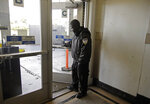 Security guard Damoi Shilon closes a door at the Greyhound bus terminal on Tuesday, Feb. 4, 2020, in Oakland, Calif.  A shooting on a Greyhound bus in California this week illustrates a stark reality about security on other modes of mass transportation in the U.S., those determined to carry out an attack on a bus, train and subway would likely face few if any security checks from any time before or after they take their seats. (AP Photo/Ben Margot)