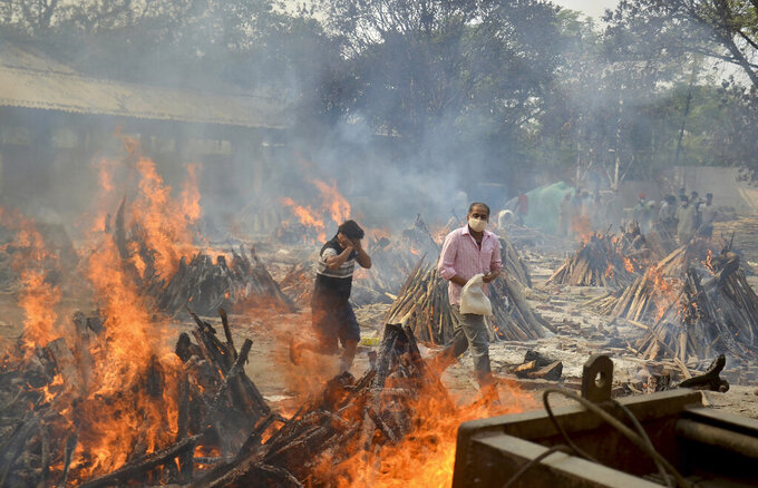 FILE - In this April 29, 2021, file photo, relatives react to heat emitting from the multiple funeral pyres of COVID-19 victims at a crematorium in the outskirts of New Delhi, India. COVID-19 infections and deaths are mounting with alarming speed in India with no end in sight to the crisis. People are dying because of shortages of bottled oxygen and hospital beds or because they couldn't get a COVID-19 test. (AP Photo/Amit Sharma, File)