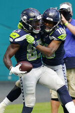 Seattle Seahawks wide receiver Tyler Lockett (16) wide receiver David Moore (83) after Moore scored a touchdown, during the second half of an NFL football game against the Miami Dolphins, Sunday, Oct. 4, 2020, in Miami Gardens, Fla. (AP Photo/Lynne Sladky)