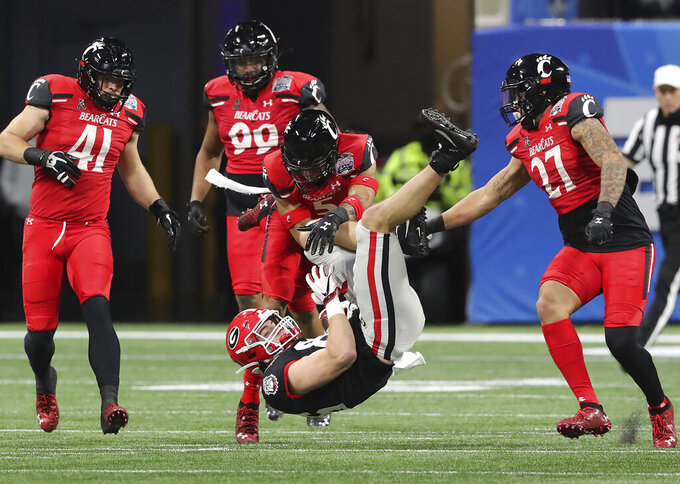 Georgia tight end John FitzPatrick is upended by Cincinnati safety Derrick Forrest after picking up a first down in the NCAA college football Peach Bowl game on Friday, Jan. 1, 2021, in Atlanta. (Curtis Compton/Atlanta Journal-Constitution via AP)
