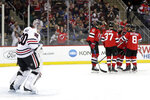 Chicago Blackhawks goaltender Cam Ward, far left, looks on as New Jersey Devils players celebrate a goal by New Jersey Devils right wing Kyle Palmieri (21) during the second period of an NHL hockey game, Monday, Jan. 14, 2019, in Newark, N.J. (AP Photo/Julio Cortez)