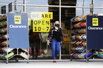 A worker wears mask as she waits for customers outside a DSW Designer Shoe store in Northbrook, Ill., Friday, May 29, 2020. Every region of Illinois met the criteria to move into Phase 3 of reopening Friday, May 29. Most of the state will do so, but Chicago will have to wait until June 3 to partially reopen. Starting Friday, more businesses such as retail, offices, manufacturing, barbershops and salons will be allowed to reopen and people can start gathering in small groups while social distancing and face covering will also be necessary. (AP Photo/Nam Y. Huh)