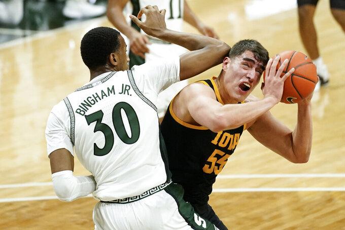 Iowa center Luka Garza (55) drives on Michigan State forward Marcus Bingham Jr. (30) in the first half of an NCAA college basketball game in East Lansing, Mich., Saturday, Feb. 13, 2021. (AP Photo/Paul Sancya)