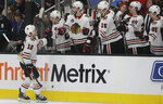 Chicago Blackhawks left wing Alex DeBrincat (12) is congratulated by teammates after scoring a goal against the San Jose Sharks during the first period of an NHL hockey game in San Jose, Calif., Thursday, March 28, 2019. (AP Photo/Jeff Chiu)
