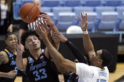 Marquette forward Dawson Garcia (33) and North Carolina forward Garrison Brooks, right, reach for a rebound during the first half of an NCAA college basketball game in Chapel Hill, N.C., Wednesday, Feb. 24, 2021. (AP Photo/Gerry Broome)