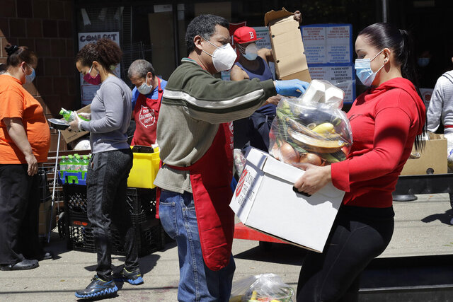 A Salvation Army worker, center, wears a mask and gloves out of concern for the coronavirus while distributing food to a person, right, also wearing a mask, Thursday, May 14, 2020 in Chelsea, Mass. (AP Photo/Steven Senne)