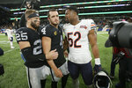 Chicago Bears outside linebacker Khalil Mack (52) talks with Oakland Raiders free safety Erik Harris (25) and quarterback Derek Carr (4) following an NFL football game at Tottenham Hotspur Stadium, Sunday, Oct. 6, 2019, in London. Oakland won 24-21. (AP Photo/Tim Ireland)