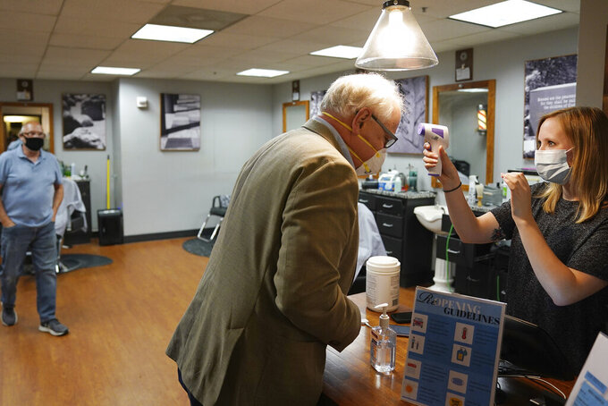 Minnesota Gov. Tim Walz gets his temperature checked by Erin Diede as he stopped in for a haircut Friday, June 5, 2020 at Capitol Barbers in the Minnesota State Office Building in St. Paul, Minn. Walz toured some of the sites that were damaged during the George Floyd protests. Floyd who died after being restrained by Minneapolis police officers on May 25. (Anthony Souffle/Star Tribune via AP)