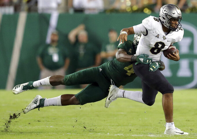 Central Florida's Darriel Mack Jr., right, fights off a tackle from South Florida's Greg Reaves during the second half of an NCAA college football game Friday, Nov. 23, 2018, in Tampa, Fla. (AP Photo/Mike Carlson)