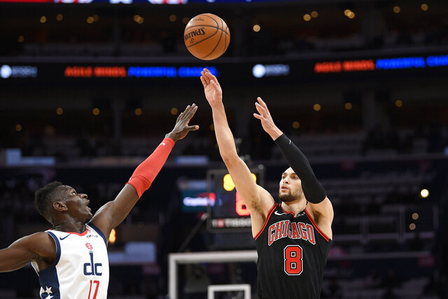 Chicago Bulls guard Zach LaVine (8) shoots next to Washington Wizards guard Isaac Bonga (17) during the first half of an NBA basketball game Wednesday, Dec. 18, 2019, in Washington. (AP Photo/Nick Wass)