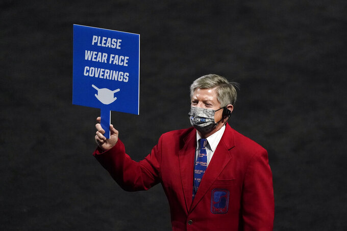 A stadium worker holds a sign instructing fans to wear face coverings during the first half of a first-round game between Oklahoma and Missouri in the NCAA men's college basketball tournament at Lucas Oil Stadium, Saturday, March 20, 2021, in Indianapolis. (AP Photo/Darron Cummings)