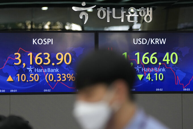 A currency trader walks by screens showing the Korea Composite Stock Price Index (KOSPI), left, and the foreign exchange rate between U.S. dollar and South Korean won at a freign exchange dealing room in Seoul, South Korea, Thursday, Sept. 16, 2021. Stocks were mostly lower in Asia on Thursday after Japan and China released data that were weaker than expected. (AP Photo/Lee Jin-man)