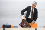 In this Friday, May 10, 2019 FILE photo, Swiss Federal Attorney Michael Lauber packs his pocket at the end of a media conference at the Media Centre of the Federal Parliament in Bern, Switzerland. According to media reports, Lauber offered his resignation on 24 July 2020 amid impeachment proceedings over his handling of the FIFA corruption probe. (Peter Klaunzer/Keystone via AP)