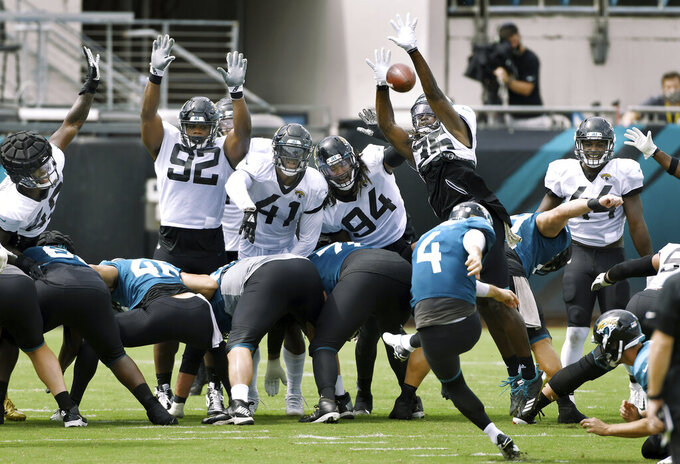 Jacksonville Jaguars defensive players Caraun Reid (92),  Josh Allen (41), Dawuane Smoot (94) and Ronnie Harrison (36)  trie to block kicker Josh Lambo's (4) field goal attempt during NFL football training camp, Saturday, Aug. 29, 2020, in Jacksonville, Fla. (Bob Self/The Florida Times-Union via AP)