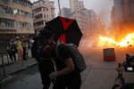 Protestors make fire to block traffic in Hong Kong, Sunday, Oct. 20, 2019. Hong Kong protesters flooded the city's streets on Sunday in defiance of a ban by the authorities on their march, setting up roadblocks and tossing firebombs amid the firing of tear gas by police. (AP Photo/Kin Cheung)