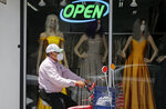 A cyclist passes a display window with mask covered mannequins at a dress store, Thursday, July 30, 2020, in McAllen,Texas. (AP Photo/Eric Gay)