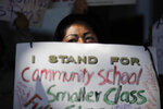 Manuela Panjoj, 42-year-old mother of five children, holds a sign during a news conference outside the Los Angeles Unified School District headquarters Wednesday, Jan. 9, 2019, in Los Angeles, Calif. The union representing teachers in Los Angeles has postponed the start of a possible strike until Monday because of uncertainty over whether a judge would order a delay. (AP Photo/Jae C. Hong)