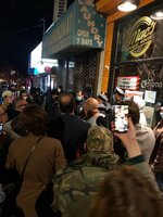 Protesters gather around police officers outside Mac's Public House on Tuesday, Dec. 1, 2020, on Staten Island, N.Y. An owner of the New York City bar that was providing indoor service in defiance of coronavirus restrictions was arrested after a sting in which plainclothes officers went inside and ordered food and beverages, the city sheriff's office said.  (Rob DeLuca/Staten Island Advance via AP)