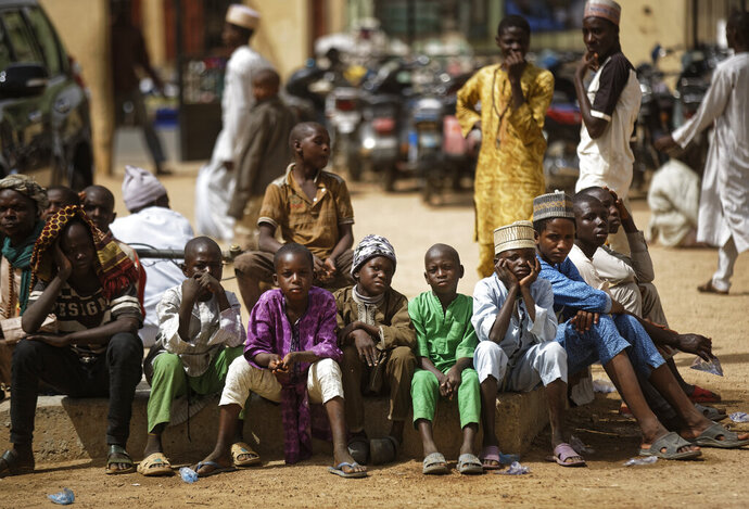 Young Muslim boys wait for traditional Friday prayers to begin at a mosque near to the Emir's palace a day prior to the start of the elections, in Kano, northern Nigeria, Friday, Feb. 15, 2019. Nigeria is due to hold general elections on Saturday, pitting incumbent President Muhammadu Buhari against leading opposition presidential candidate Atiku Abubakar. (AP Photo/Ben Curtis)